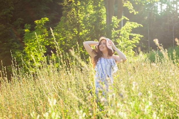 帽子とドレスを着た長い髪の幸せな若い女性は、晴れた日に夏の森を歩いている間、植物に向かって手を引っ張る。夏の喜び