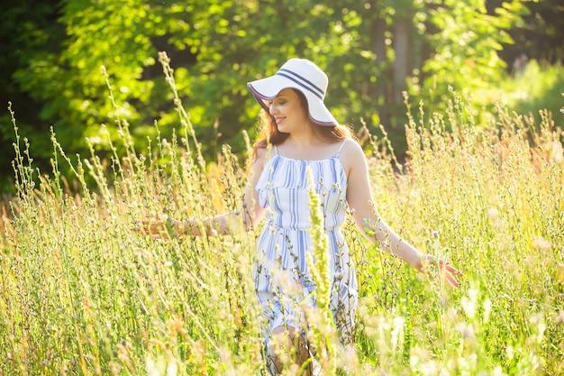帽子とドレスの長い髪の幸せな若い女性は歩きながら植物に向かって手を引っ張る