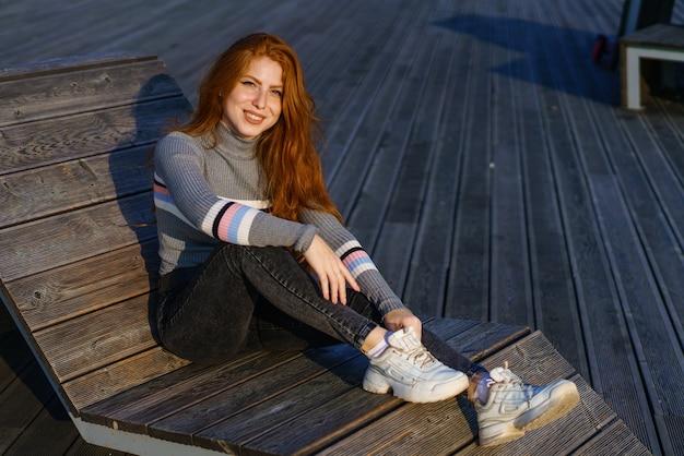 晴れた日に長い赤い髪の幸せな若い女性が公園のウッドデッキでカジュアルな服を着て座って笑っている