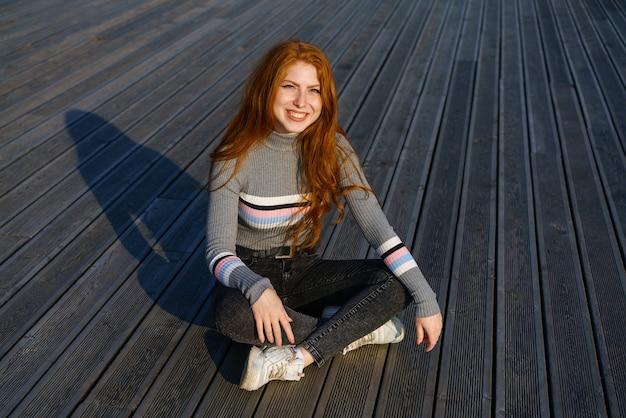 白人国籍の長い赤髪の幸せな若い女性は、paでカジュアルな服を着て座っています