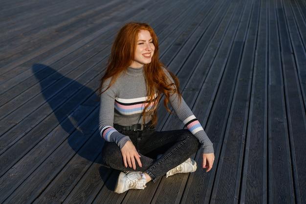 白人国籍の長い赤髪の幸せな若い女性が公園でカジュアルな服を着て座っています