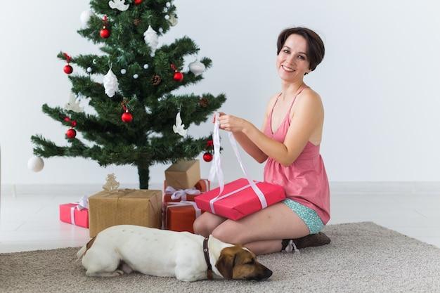 Счастливая молодая женщина с прекрасной собакой открывая настоящую коробку под рождественской елкой.