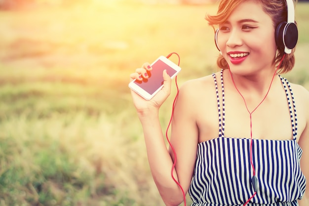 Счастливый молодая женщина с мобильным и наушники