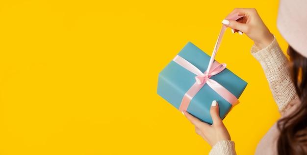 クリスマスプレゼントのギフトボックスを開いて口を開けて幸せな若い女性、女の子はギフトボックスを覗き込み、幸せに笑います。新年とクリスマスのための贈り物と驚きの概念。