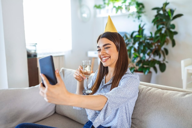 Happy young woman with a party hat having video conference online meeting with friends and family