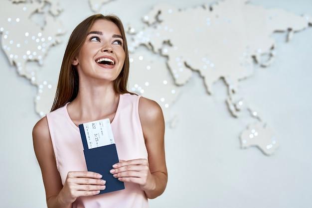 Счастливая молодая женщина с паспортами и билетами в офисе туристической компании