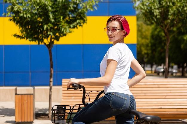 ピンクの髪を持つ幸せな若い女性は、夏に自転車で街を歩きます。