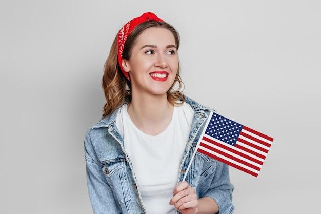 赤い口紅を持った幸せな若い女性は、灰色の壁に孤立した小さなアメリカの国旗と笑顔を持っています、アメリカの国旗を持っている女の子、7月4日の独立記念日、コピースペース