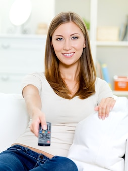 Happy young woman with remote control sitting on the sofa and watching tv