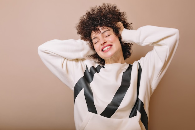 Happy young woman with ringlets closed eyes with lovely smile and poses on beige with white pullover