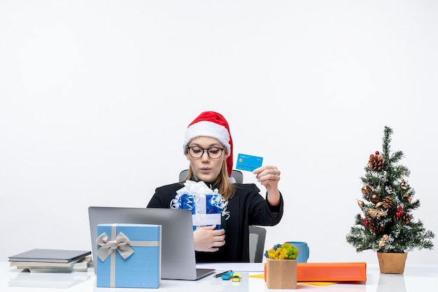 Happy young woman with santa claus hat and wearing eyeglasses sitting at a table holding christmas gift and bank card on white background footage