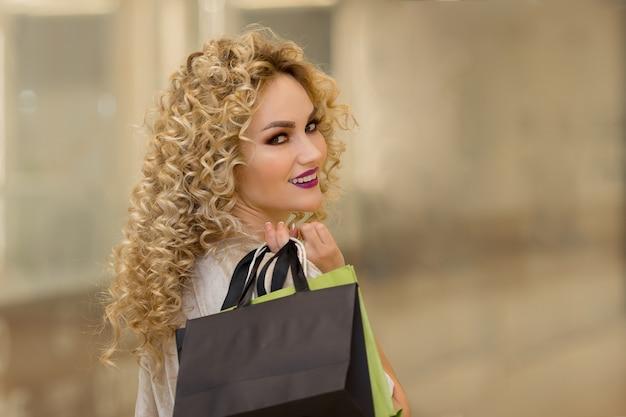 쇼핑몰에서 쇼핑백을 든 행복한 젊은 여성이 돌아섰다. 판매, 소비 및 사람 개념