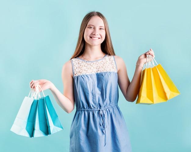 青色の背景に分離された買い物袋を持つ幸せな若い女性