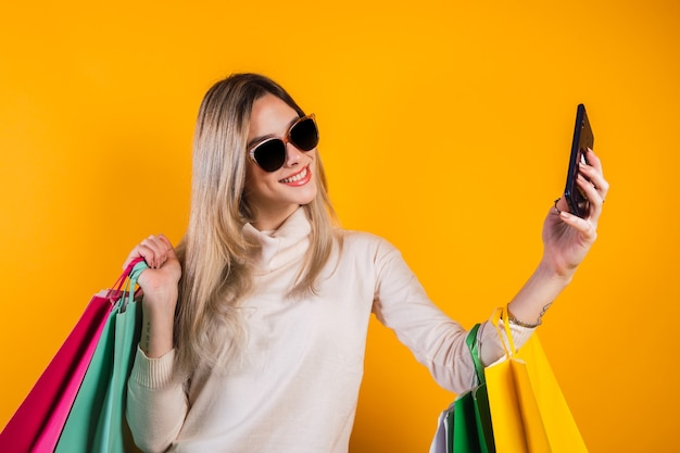 노란색 배경에 셀카를 찍는 쇼핑백을 든 행복한 젊은 여성.