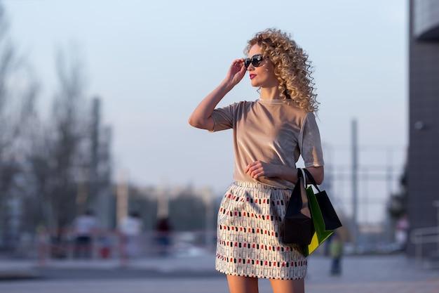 街の通りを歩いて買い物袋を持つ幸せな若い女性。販売、消費主義、人々の概念