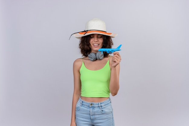 A happy young woman with short hair in green crop top wearing sun hat looking at a blue toy airplane on a white background