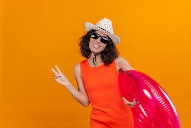 Una giovane donna felice con i capelli corti in una camicia arancione che porta il cappello del sole e gli occhiali da sole che tengono l'anello gonfiabile che mostra un gesto di due dita