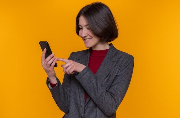 Счастливая молодая женщина с короткими волосами, одетая в серый пиджак, держит смартфон, печатая различные сообщения