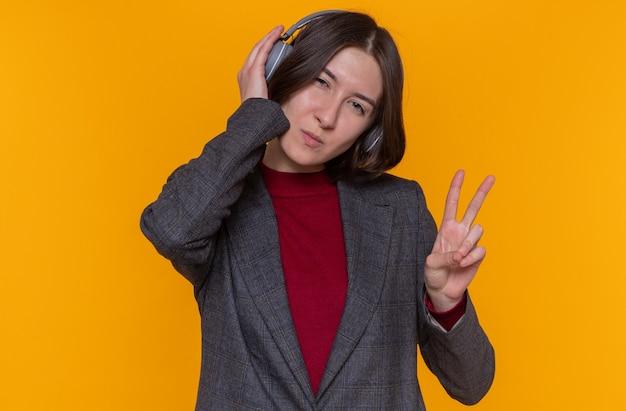 Felice giovane donna con i capelli corti che indossa giacca grigia
