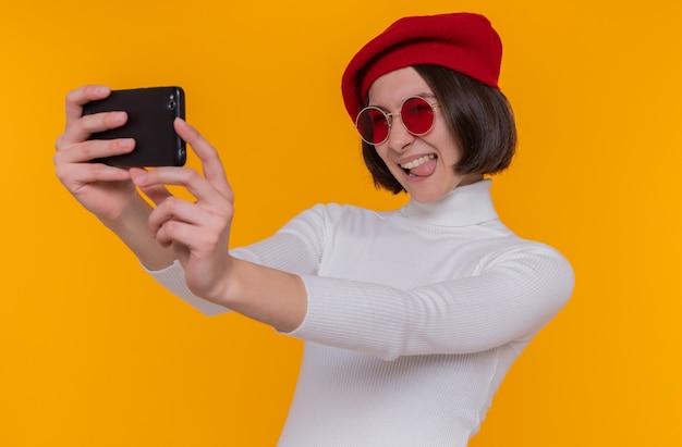 Felice giovane donna con i capelli corti in dolcevita bianco che indossa berretto e occhiali da sole rossi facendo selfie utilizza lo smartphone sorridendo allegramente in piedi sopra la parete arancione