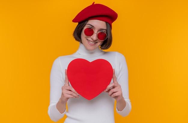 Felice giovane donna con i capelli corti in dolcevita bianco che indossa berretto e occhiali da sole rossi tenendo il cuore fatto di cartone guardando la parte anteriore sorridente allegra in piedi sopra la parete arancione
