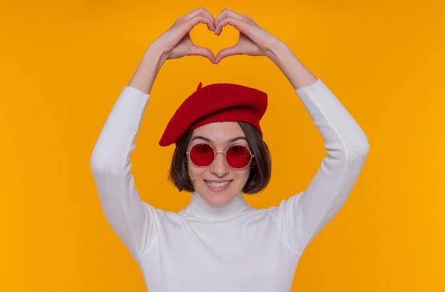 Felice giovane donna con i capelli corti in dolcevita bianco che indossa berretto e occhiali da sole rossi sorridendo allegramente facendo il gesto del cuore con le dita sopra la sua testa in piedi sopra la parete arancione