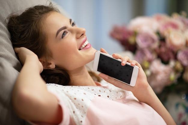 家で夢を見ているスマートフォンを持つ幸せな若い女性。魅力的な女性が携帯電話を持っている-屋内。