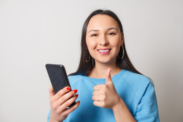 A happy young woman with a smartphone in her hand shows a thumbs-up gesture. on a white background.