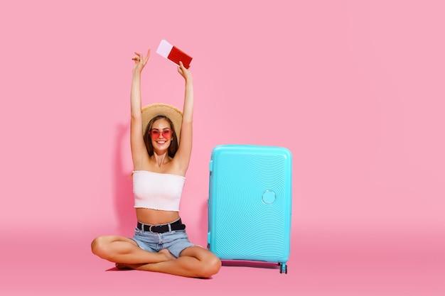 Счастливая молодая женщина с чемоданом, билетами, деньгами и паспортом собирается путешествовать, концепция путешествия
