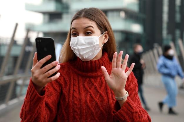 街の通りを歩いているときにサージカルマスクのビデオ通話で幸せな若い女性