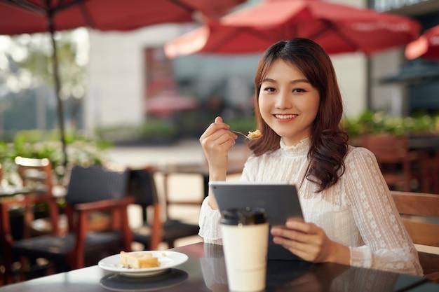 Счастливая молодая женщина с планшетным компьютером на террасе городского уличного кафе