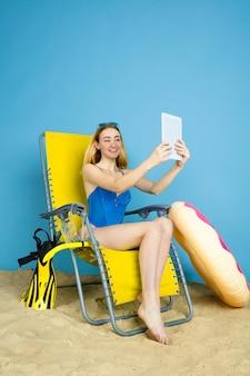 Felice giovane donna con tablet prende selfie o vlog sui viaggi su sfondo blu studio. concetto di emozioni umane, espressione facciale, vacanze estive, fine settimana. estate, mare, oceano, alcol.