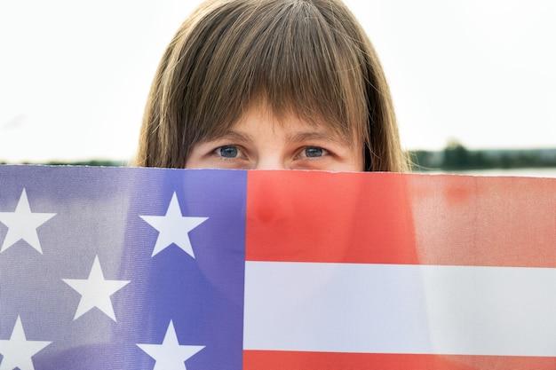 Счастливая молодая женщина с национальным флагом сша в руке