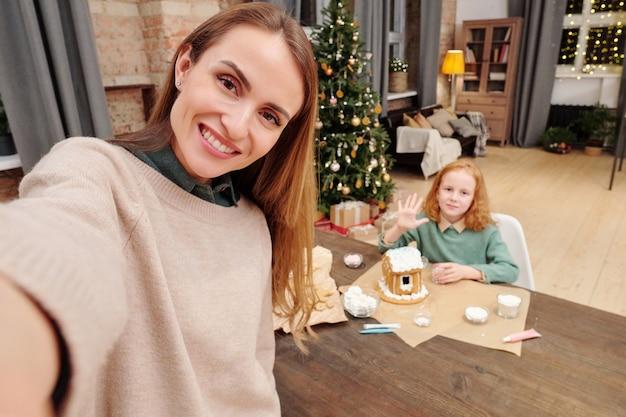 크리스마스 디저트를 준비하는 동안 손을 흔들며 그녀의 귀여운 작은 딸에 대한 카메라 앞에서 셀카를 만드는 이빨 미소로 행복 한 젊은 여자