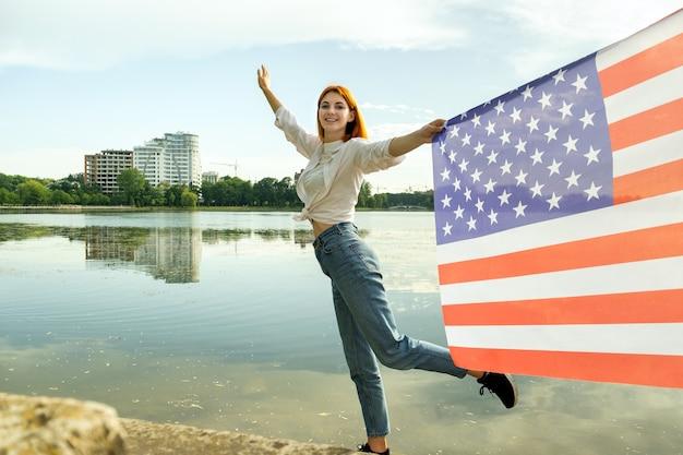 그녀의 손에 미국 국기와 함께 행복 한 젊은 여자. 미국 독립 기념일을 축하하는 긍정적인 소녀. 국제 민주주의의 날 개념.