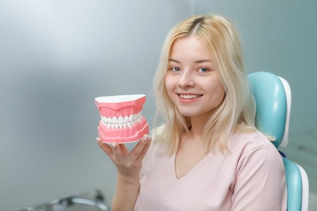 Счастливая молодая женщина с белыми здоровыми зубами, держащая модель челюсти, сидя в стоматологическом кресле