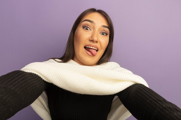 혀를 튀어 나와 흰색 스카프로 행복 한 젊은 여자