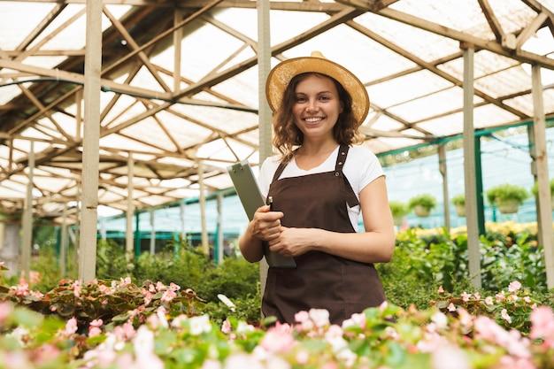 온실에서 일하는 행복 한 젊은 여자