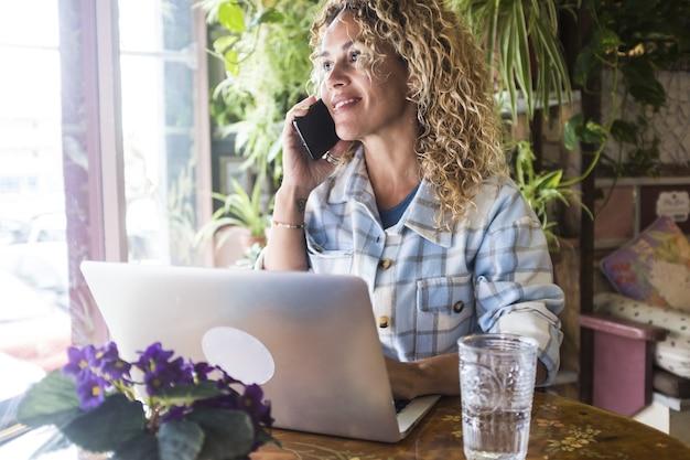 ラップトップで作業し、携帯電話で話している幸せな若い女性。自宅で働く実業家。ノートパソコンとテーブルの上のガラスを飲むと携帯電話で話している笑顔の女性