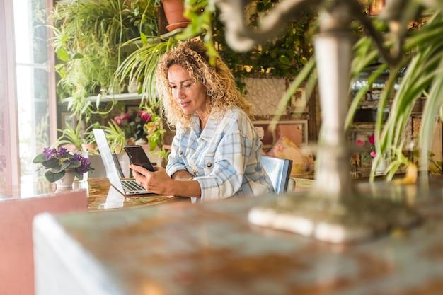 ラップトップと携帯電話のテキストメッセージに取り組んでいる幸せな若い女性。自宅で働く実業家。机の上にラップトップで携帯電話を使用してメディアコンテンツを見ている女性