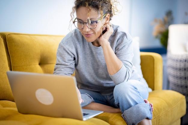 소파에 앉아 노트북 작업을 하는 행복 한 젊은 여자. 집에서 일하는 여자. 안경을 쓰고 다리를 꼬고 앉아 있는 젊은 여성.