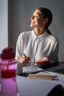 Счастливая молодая женщина, писать в тетради и держа смартфон, сидя за столом