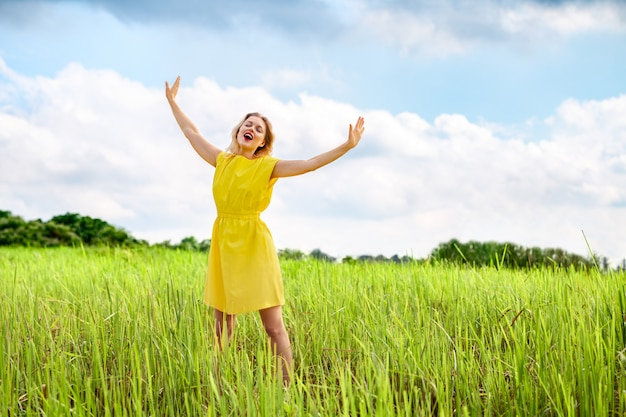 Happy young woman in yellow dress is singing with closed eyes and raising her hands on green meadow.
