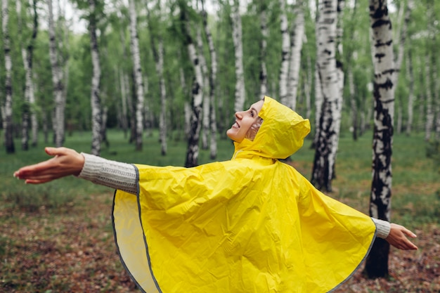Happy young woman in yellow raincoat walking in spring forest and having fun raising arms