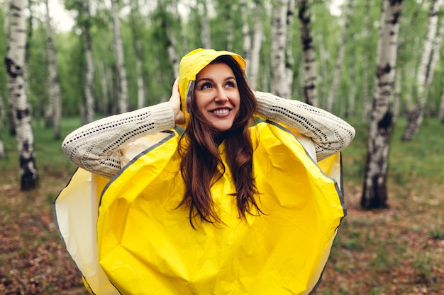 Happy young woman in yellow raincoat walking in spring forest and having fun
