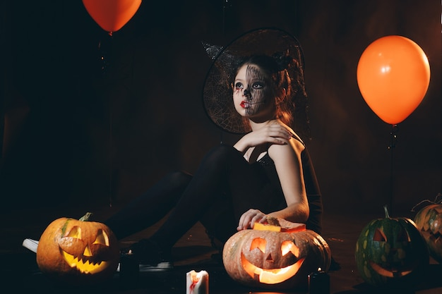 Happy young women in black witch halloween costumes on party