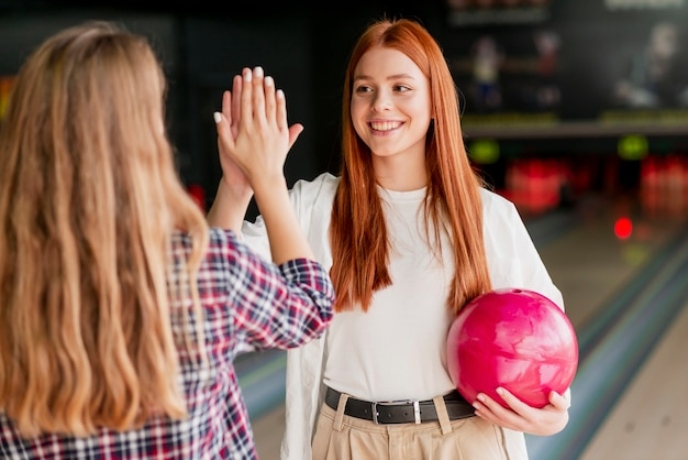 Giovani donne felici nel randello di bowling