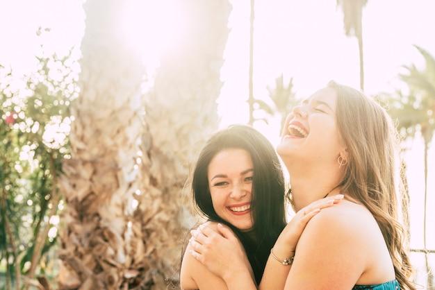 幸せな若い女性の友人は、フレンドリーな抱擁で一緒に楽しみ、笑う