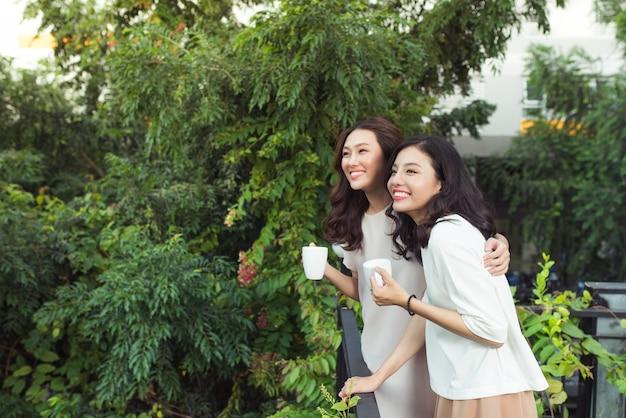 행복 한 젊은 여자 친구는 함께 서있는 동안 웃 고 잘 입고
