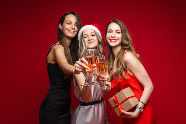 Happy young women friends with gift and champagne celebrating holiday together on party on red background, copy space